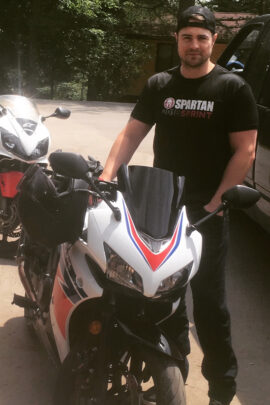 Trevor standing with motorcycle